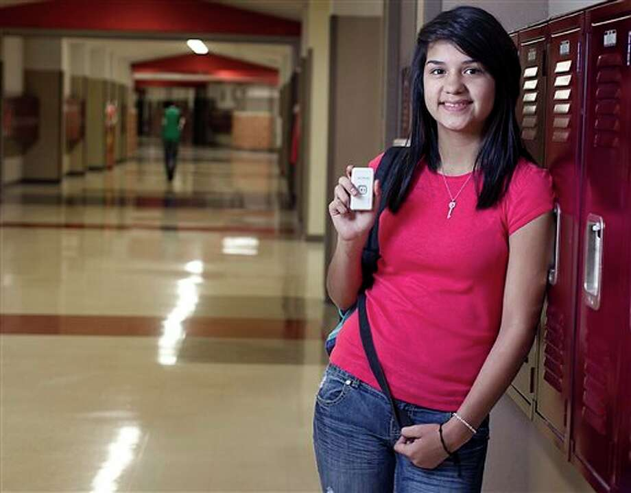 In this Dec. 11, 2012 photo, Marisol Castro Soto, 16, a sophomore at Akins High School, holds a student GPS tracker she uses to record her location and attendance at school in Austin, Texas. Akins High School sophomore Marisol Castro Soto said she had fallen in with the wrong crowd. She and her friends would frequently skip school or show up to classes at their leisure. But when the 16-year-old was threatened with going before a judge because of her absences, Marisol knew it was time for a change. She volunteered for the Austin school district's new truancy program, which uses GPS trackers to help prompt students to go to class more often. (AP Photo/Statesman.com, Rodolfo Gonzalez) MAGS OUT; NO SALES; INTERNET AND TV MUST CREDIT PHOTOGRAPHER AND STATESMAN.COM Photo: Rodolfo Gonzalez / AUSTIN AMERICAN-STATESMAN