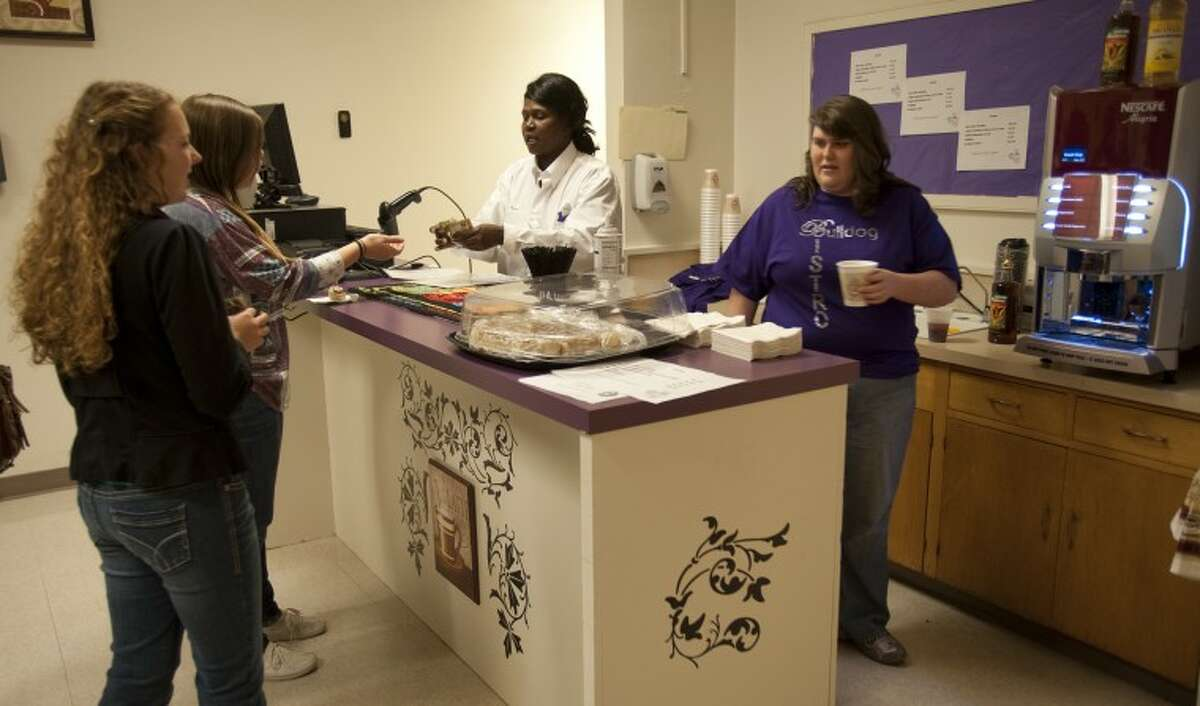 Amber Coyle gets a coffee drink ready as MHS teacher Laura Marion works the register Monday for MHS student Sophia Martinez and Kristen Dunlap at the newly opened Bulldog Bistro Cafe at Midland High.