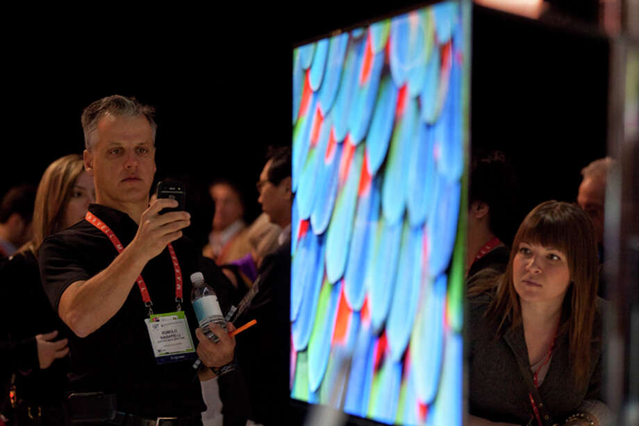 FILE - In this Jan. 10, 2012 file photo, industry affiliates examine the new Samsung 55-inch OLED television during the 2012 International CES trade show, in Las Vegas. The International Consumer Electronics show gathered more than 140,000 people in Las Vegas this week. These are some of the more significant gadgets that were announced at the show, (AP Photo/Julie Jacobson, File) Photo: Julie Jacobson / AP