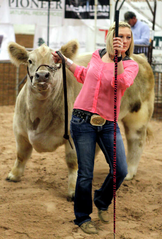 Savannah Cain, a student at Greenwood High School, shows off her championship steer during a charity auction event of the Midland County Livestock Show Saturday at Horseshoe Arena. The steer raised $10,000. James Durbin/Reporter-Telegram Photo: JAMES DURBIN / © 2012 Midland Reporter Telegram. All Rights Reserved.