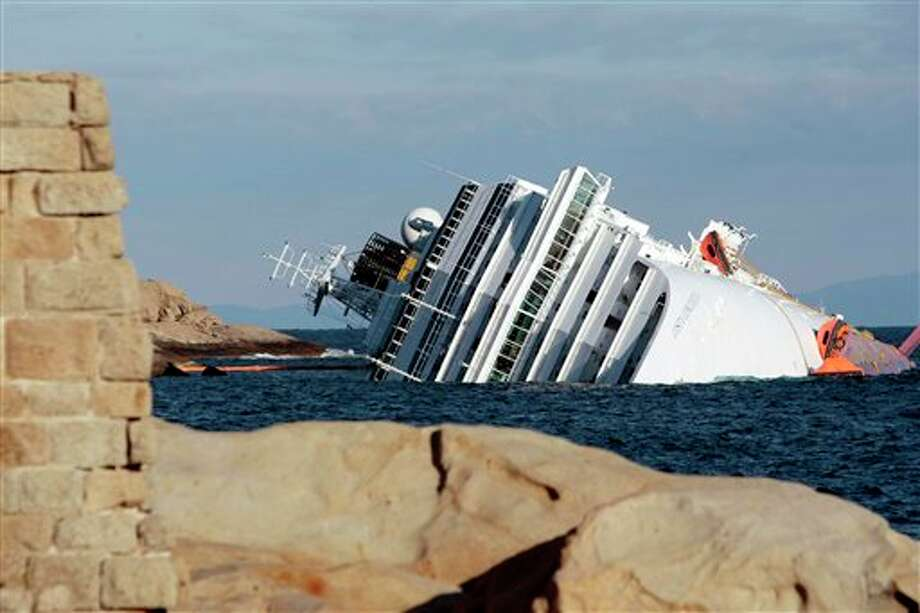 "The cruise ship Costa Concordia leans on its side Tuesday, Jan. 17, 2012, after running aground on the tiny Tuscan island of Giglio, Italy, on Friday evening. Italian naval divers on Tuesday exploded holes in the hull of a cruise ship that grounded near a Tuscan island to speed the search for 29 missing passengers and crew while the seas remain relatively calm. The search intensified as prosecutors prepared to question the captain, who is accused of causing the wreck that left at least six dead by making a maneuver that the Italian cruise operator said was ""unapproved and unauthorized."" Photo: Gregorio Borgia 
