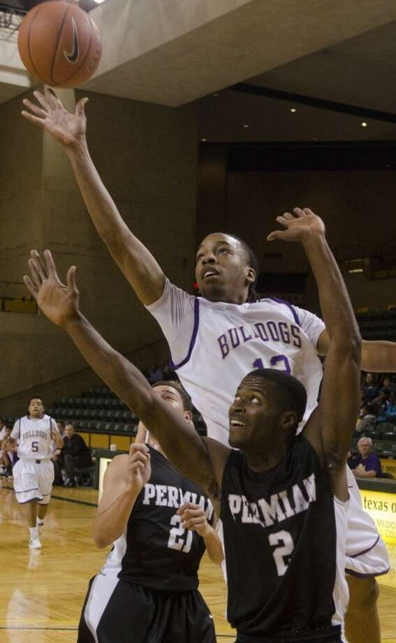 Midland High's T.J. Brown splits Permian defenders, Jorrion Wilson (2) and Dominique Krumnow (21) on Jan. 17 at Chap Center. Photo: Tim Fischer