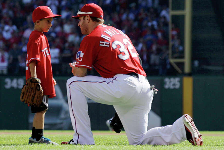 FILE - IN This Sept. 30, 2011, file photo, Cooper Stone, 6, left, talks with Texas Rangers left fielder Josh Hamilton (32) before Game 1 of baseball's American League division series playoffs in Arlington, Texas. Hamilton threw the ball Cooper's father Shannon Stone was reaching for when he fell to his death behind the outfield wall in July. Shannon Stones mother said Wednesday, Dec. 28, 2011, in Lubbock, Texas, that she wants the star player to keep tossing souvenirs into the stands. (AP Photo/Tony Gutierrez, File) Photo: Tony Gutierrez / AP2011