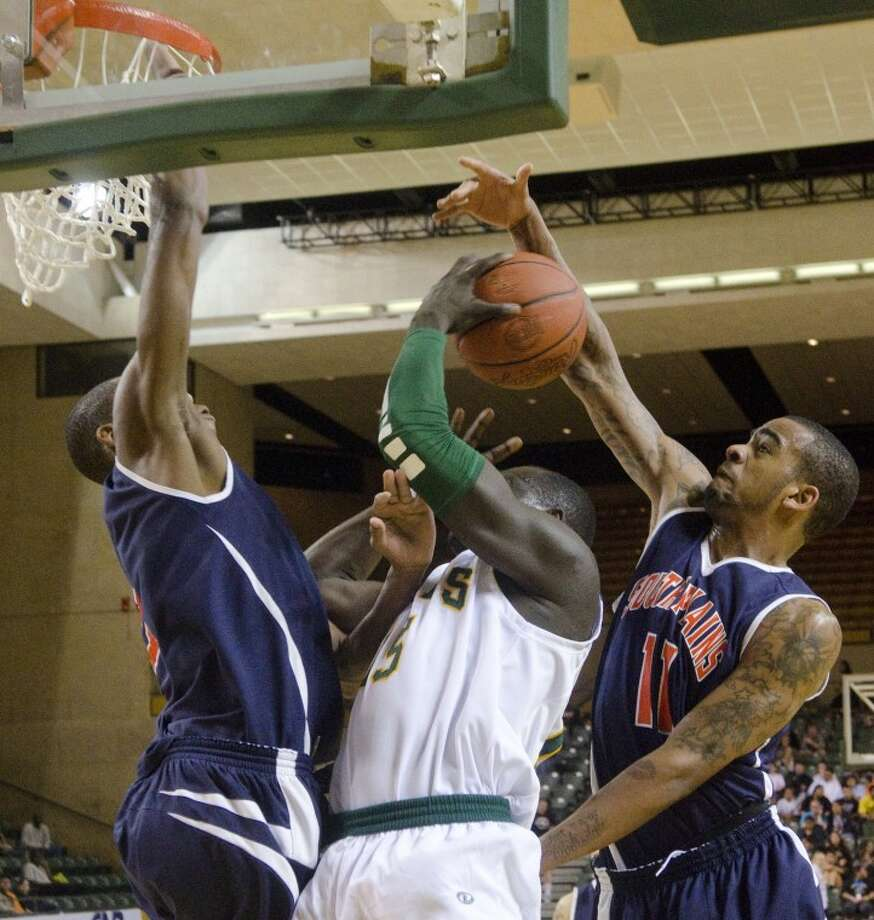 Midland College's Majok Majok takes the ball to the basket in traffic as South Plains' Yanick Moreira, left, and Stanton Kidd go for a block last Monday night at the Chap Center. Photo by Tim Fischer/Midland Reporter-Telegram Photo: Tim Fischer
