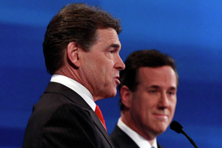Texas Gov. Rick Perry, left, speaks as former Pennsylvania Sen. Rick Santorum listens at the South Carolina Republican presidential candidate debate in Myrtle Beach, S.C., Monday, Jan. 16, 2012. (AP Photo/Charles Dharapak, Pool) Photo: Charles Dharapak / AP POOL