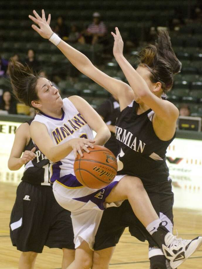 Midland High's Krystal Valdez gets knocked back trying to drive to the basket as Permian's Tailor Dominguez defends Tuesday evening at Chap Center. Photo: Tim Fischer/Reporter-Telegram