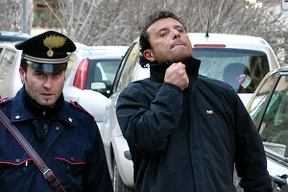 In this photo taken on Saturday, Jan. 14, 2012, and made available Wednesday, Jan. 18, 2012, Francesco Schettino, right, the captain of the luxury cruise ship Costa Concordia, which ran aground Friday off the tiny Tuscan island of Isola del Giglio, is taken into custody by Carabinieri in Porto Santo Stefano, Italy. Schettino, released on Tuesday, and currently under house arrest in his hometown of Meta di Sorrento, southern Italy, is being investigated for possible manslaughter charges and abandoning the ship. (AP Photo/Giacomo Aprili) Photo: Giacomo Aprili / AP