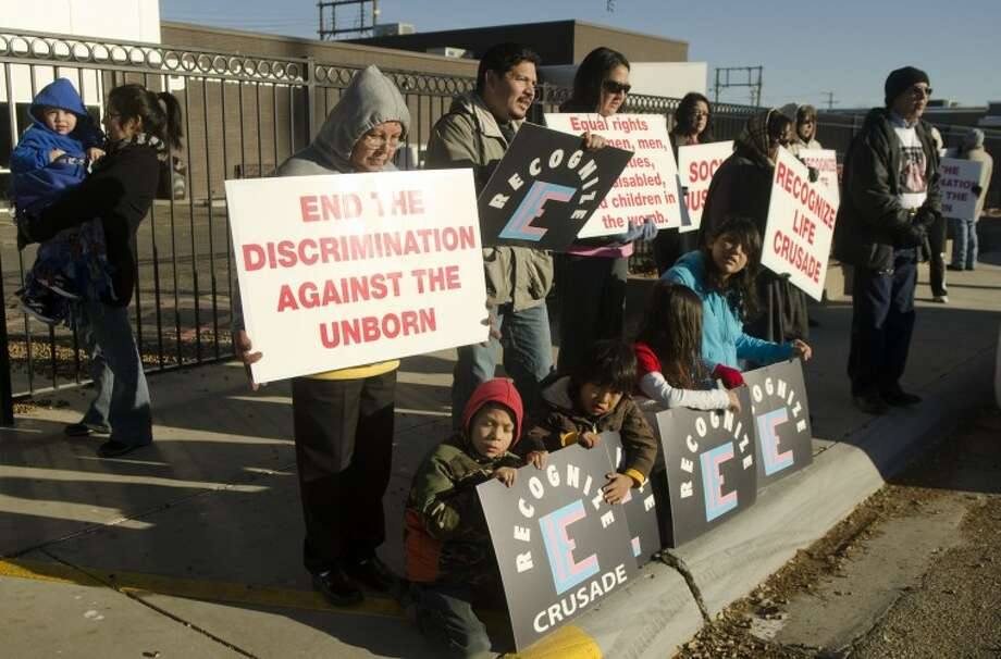 Chiuldren and adults hold signs and say the rosary Tuesday outside Planned Parenthood on Secor Street. West Texans for Life came in from Abilene to march outside the building after doing the same in Ablilene and San Angelo. Photo by Tim Fischer/Midland Reporter-Telegram Photo: Tim Fischer