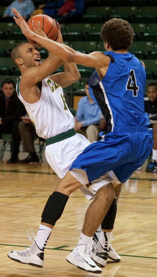 Midland College's Corey Hilliard puts a shot up but is called for a charge on Odessa College's Ladon Carnege Monday night at the Chaparral Center. Tim Fischer\Reporter-Telegram Photo: Tim Fischer