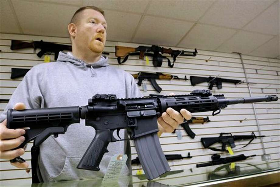 This Jan. 16 file photo shows John Jackson, co-owner of Capitol City Arms Supply, with an AR-15 rifle for sale at his business in Springfield, Ill. From Oregon to Mississippi, President Barack Obama's proposed ban on new assault weapons and large-capacity magazines struck a nerve among rural lawmen and lawmakers, many of whom vowed to ignore any restrictions and even try to stop federal officials from enforcing gun policy in their jurisdictions. (AP Photo/Seth Perlman) Photo: Seth Perlman / ap