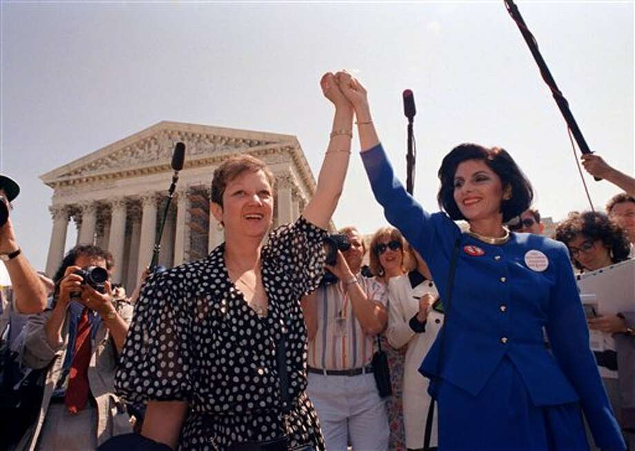 ADVANCE FOR USE SUNDAY, JAN. 20, 2013 AND THEREAFTER - FILE - In this Wednesday, April 26, 1989 file photo, Norma McCorvey, Jane Roe in the 1973 court case, left, and her attorney Gloria Allred hold hands as they leave the Supreme Court building in Washington after sitting in while the court listened to arguments in a Missouri abortion case. Months later, the high court ultimately upheld the Missouri law in the case, Webster v. Reproductive Health Service, making it illegal to use public officials or facilities for abortions. (AP Photo/J. Scott Applewhite) Photo: J. Scott Applewhite / AP