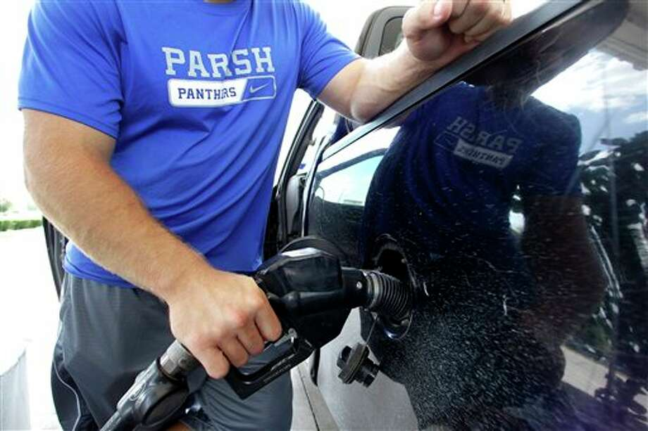 FILE - In this June 30, 2011 file photo, a motorist pumps gasoline into his vehicle at an Exxon gas station, in Farmers Branch, Texas. For the first time in months, retail gasoline prices have fallen below $3 a gallon in places, including parts of Michigan, Missouri and Texas. And the relief is likely to spread thanks to a sharp decline in crude-oil prices. (AP Photo/Tony Gutierrez, File) Photo: Tony Gutierrez / AP2011