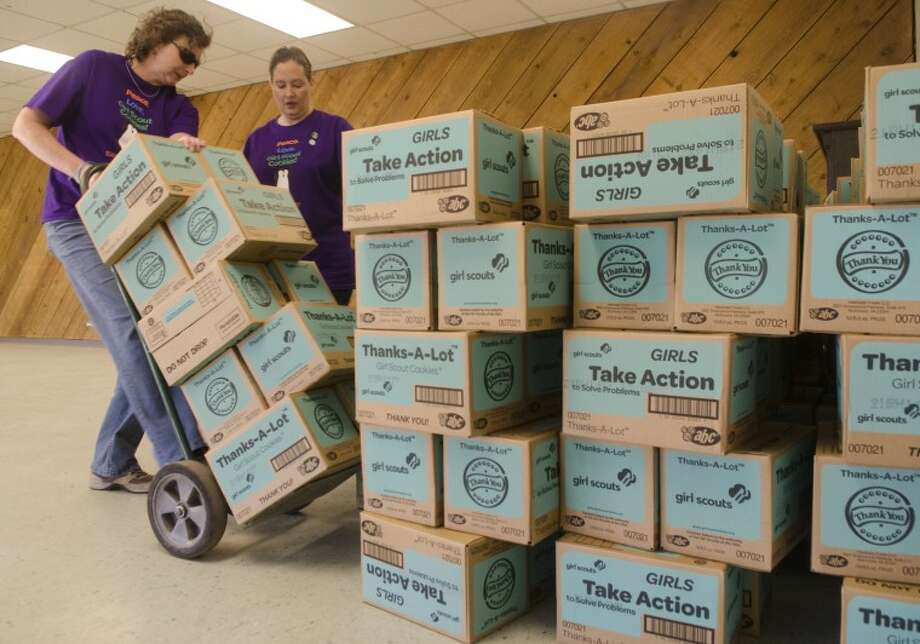 Beth Curran tips a dolly back as Tasha Riddle helps unload some of the 2387 cases of Girl Scout cookies delivered Friday morning at the Girl Scout office. Photo by Tim Fischer/Midland Reporter-Telegram Photo: Tim Fischer