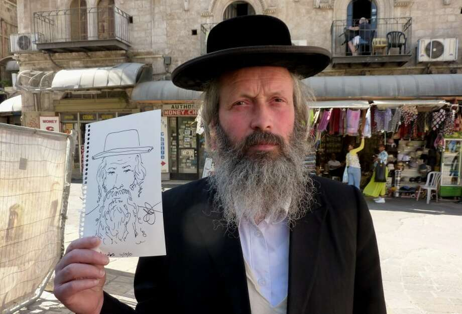 A picture of a Hebrew man holding a caricature drawn by Stan jacobs when he was in Israel