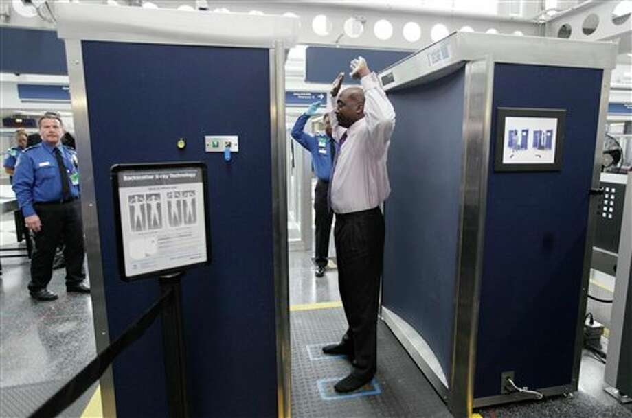 FILE - In this Monday, March 10, 2010 file photo, volunteers pass through the first full body scanner, which uses backscatter technology, installed at O'Hare International Airport in Chicago. Those airport scanners with their all-too revealing body images will soon be going away. The Transportation Security Administration says the X-ray scanners will be gone by June 2013 because the company that makes them can't fix the privacy issues. The other airport body scanners, which produce a generic outline instead of a naked image, are staying. (AP Photo/M. Spencer Green, File) Photo: M. Spencer Green / AP