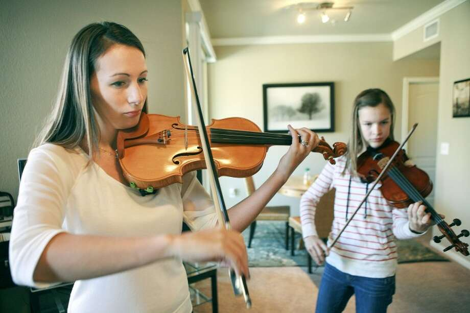 Katie Phillips, left, and her student, Sarah Lunsford, 16, play a Celtic fiddle piece Monday at Phillps' musical school. Cindeka Nealy/Reporter-Telegram Photo: Cindeka Nealy