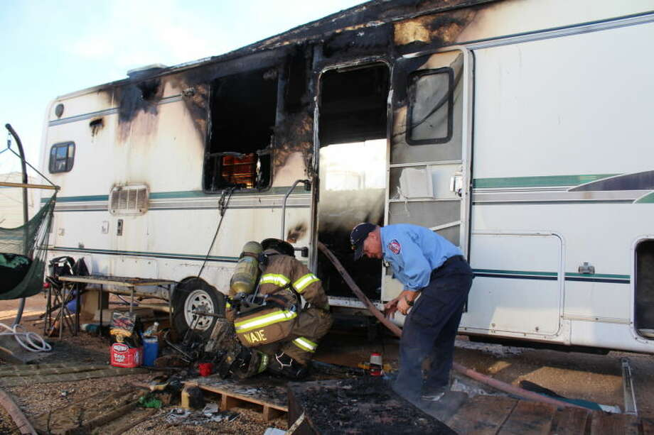 Midland Fire Department officials clean up the aftermath of a fire that destroyed a mobile home Sunday at Midland RV Park. Tyler White/Reporter-Telegram Photo: Tyler White