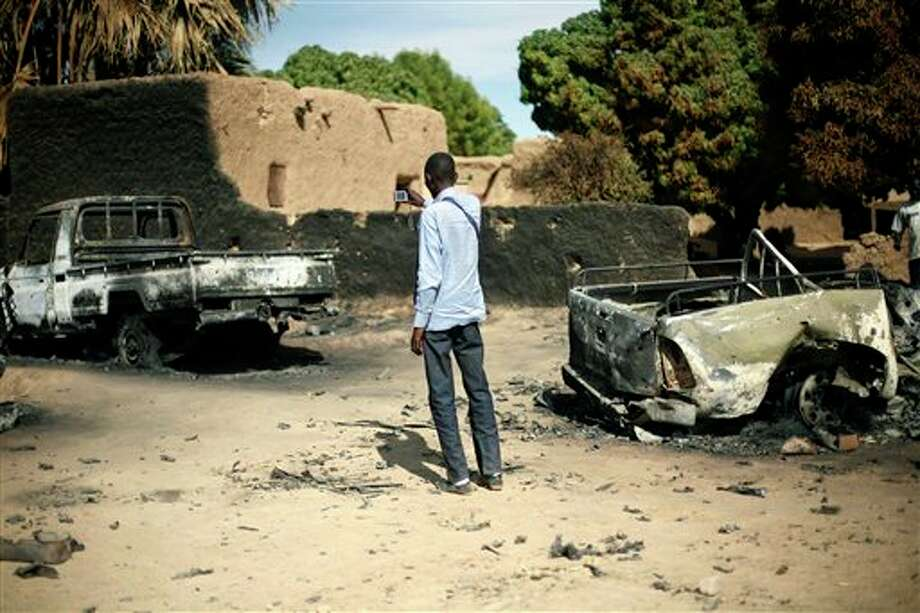 An unidentified man takes a picture of the charred remains of trucks used by radical Islamists on the outskirt of Diabaly, Mali, some 460kms (320 miles) North of the capital Bamako Monday Jan. 21, 2013. French and Malian troops took control Monday of the town of Diabaly, patrolling the streets in armored personnel carriers and inspecting the charred remains of a pickup truck with a mounted machine gun left behind by the fleeing militants. (AP Photo/Jerome Delay) Photo: Jerome Delay / AP