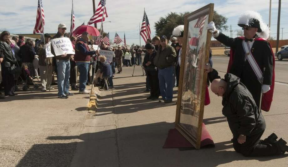 (File Photo) Bishop Michael Pfeifer prays on his knees holding a the picture o Our Lady of Guadalupe Friday outside Planned Parenthood as he and other Catholics pray for the end to abortions on the anniversary of Roe vs. Wade. Photo by Tim Fischer/Midland Reporter-Telegram Photo: Tim Fischer