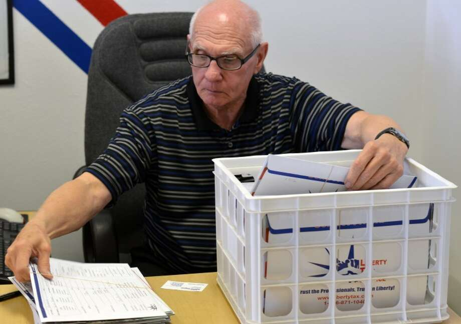 (File Photo) John Wojtkun, owner of the Liberty Tax Service on North Midkiff Road, searches through tax records in preparation for tax day on Tuesday. Photo: James Cannon/MRT