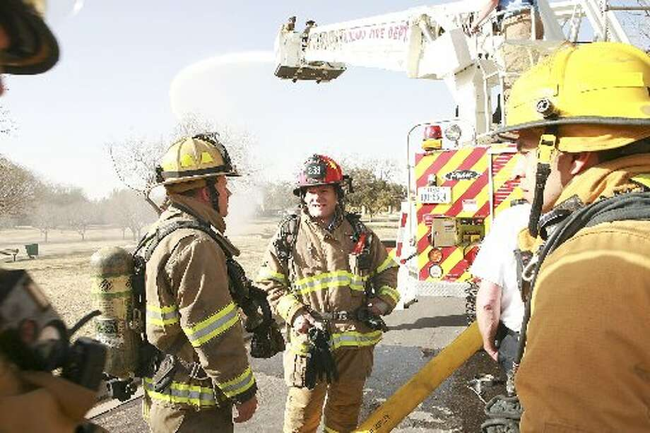Odessa Fire Department Capt. Richie Gaule, left, and Midland Capt. Aaron Cox discuss how well the two departments worked together during a water tower training exercise Thursday at Hill Park in Midland. Photo: Cindeka Nealy/Reporter-Telegram
