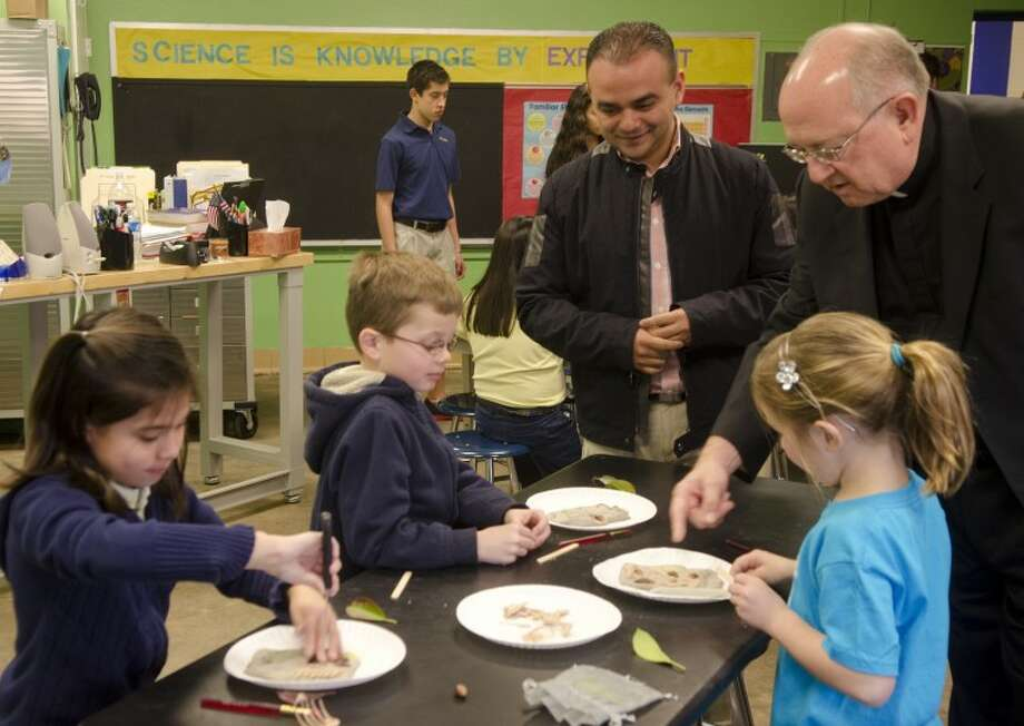 The Rev. Luis Estevez and Monsignor Larry Droll talk with students at St. Ann's School Tuesday morning. Estevez is visiting from a partner school in Honduras. Photo by Tim Fischer/Midland Reporter-Telegram Photo: Tim Fischer