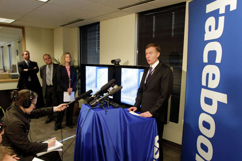 Washington state Attorney General Rob McKenna, right, talks to reporters in Seattle, Thursday, Jan. 26, 2012, during a news conference to announce a new legal strategy to combat a scam affecting Facebook users. (AP Photo/Ted S. Warren) Photo: Ted S. Warren / AP