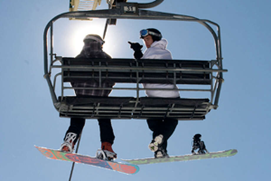 FILE - In this Nov. 8, 2011 file photo, snowboarders enjoy the blue skies and sunshine as they ride the lift at Bear Mountain Resort in Big Bear, Calif. (AP Photo/The Orange County Register, Jeb Harris, File) Photo: JEBB HARRIS / AP2011