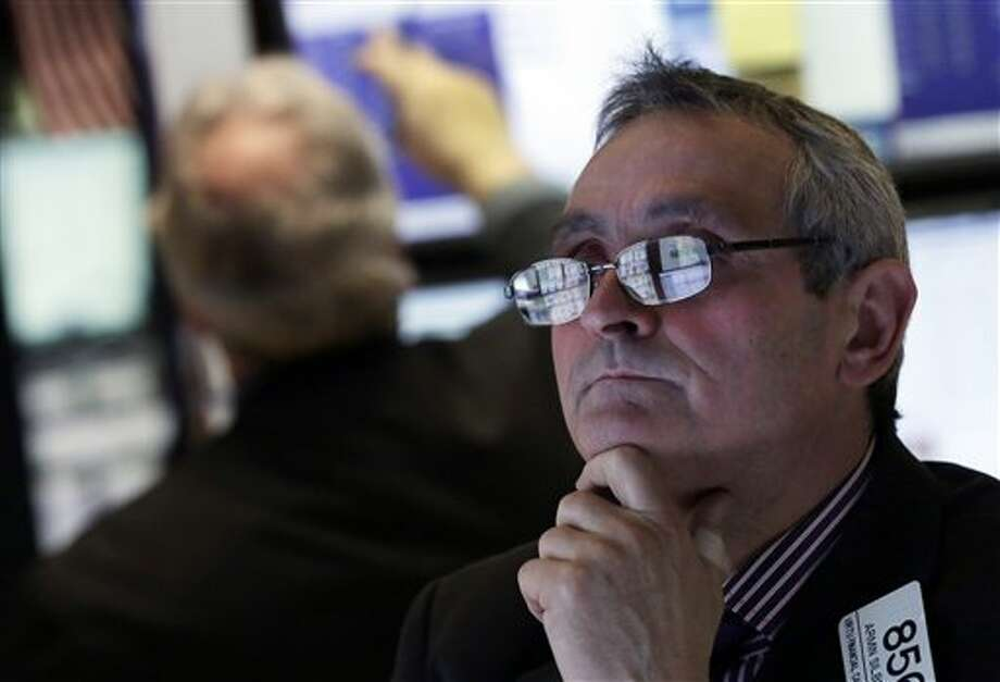 In this Wednesday, Jan. 23, 2013 photo, the screens of specialist Armin Silbersmith are reflected in his glasses as he works at his post on the floor of the New York Stock Exchange. Europe's stock markets were broadly higher Thursday Jan. 23, 2013 amid signs the continent's services and manufacturing slump was easing. (AP Photo/Richard Drew) Photo: Richard Drew / AP