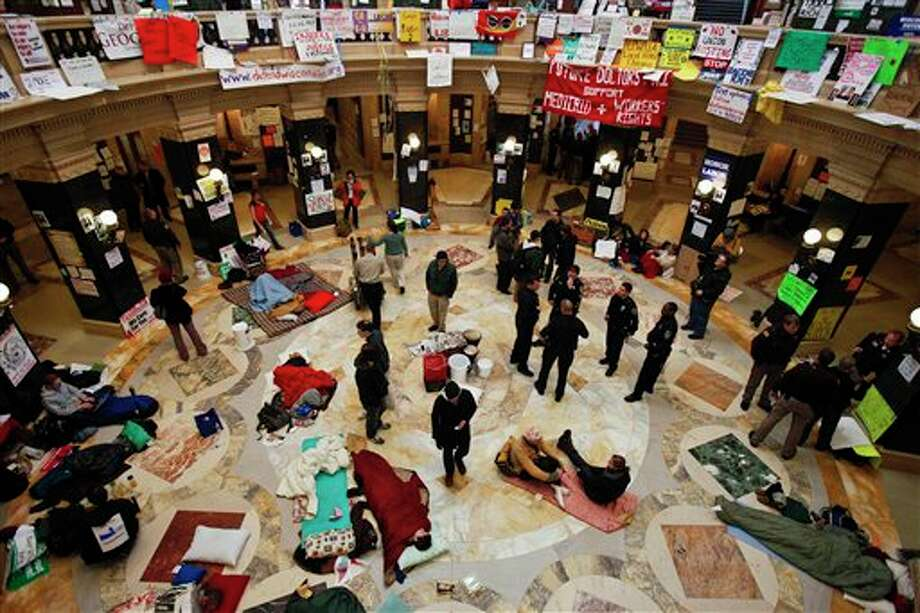 FILE - This Feb. 28, 2011 file photo shows protests continuing at the state Capitol in Madison, Wis., as police and demonstrators gather on the rotunda floor where opponents to the governor's bill to eliminate collective bargaining rights for many state workers have been sleeping. The nation's labor unions suffered sharp declines in membership last year, the Bureau of Labor Statistics said Wednesday, led by losses in the public sector as cash-strapped state and local governments laid off workers and _ in some cases _ limited collective bargaining rights. (AP Photo/Andy Manis, File) Photo: Andy Manis / FR19153 AP