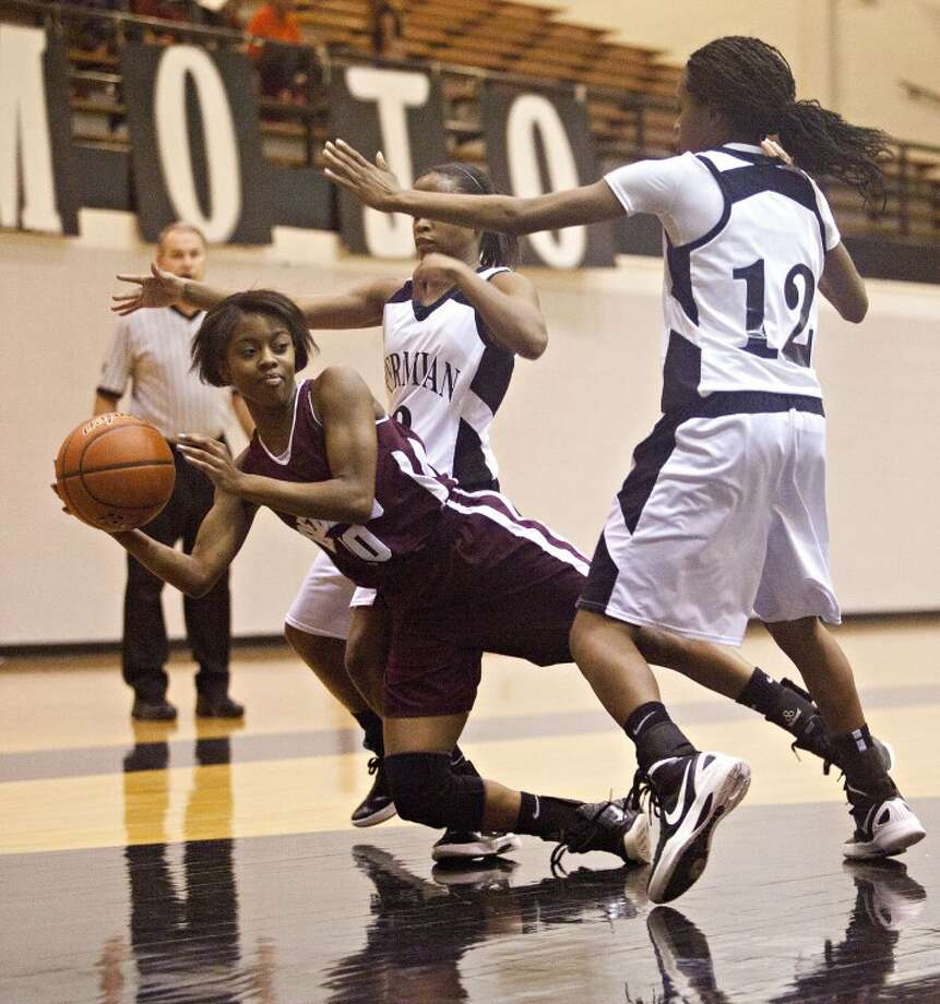 Midland Lee's Daija Stanford (10) falls while passing the ball as Permian's Cheyenne Swoopes (12) and Jamia Graham (3) trap her during the game Friday at the Permian Fieldhouse. Albert Cesare|Odessa American