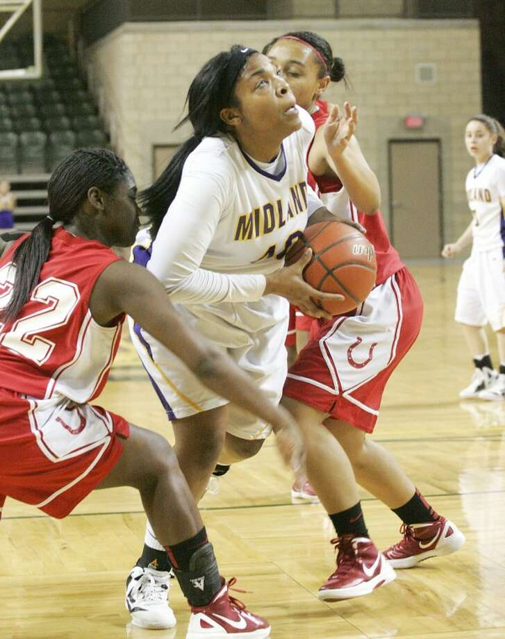 Midland High's Sabrina Banks (40) looks up to attempt the shot for two as she's guarded by Odessa's LaTanya MacMarion (22) and Marie Dechant (42) earlier this year at Chaparral Center. Cindeka Nealy/Reporter-Telegram Photo: Cindeka Nealy
