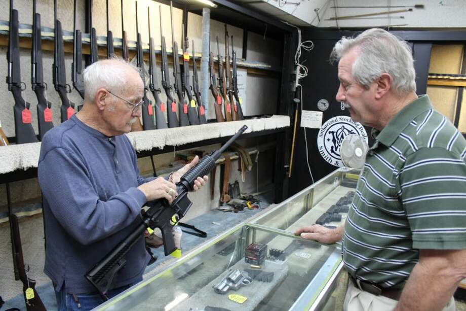 "(File Photo) Tommy ""Hoss Fly"" Atchison, owner of Guns & Trades Inc., shows a DPMS AR-15 semi-automatic rifle to Midlander Aubrey Glosson Monday at his shop. Tyler White/Reporter-Telegram Photo: Tyler White"