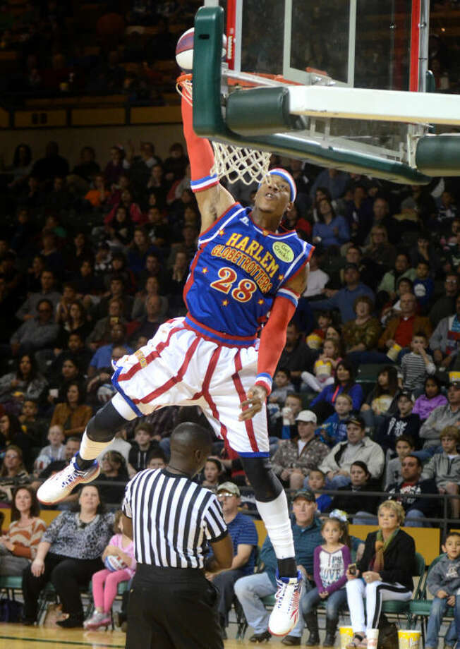 Harlem Globetrotter Hacksaw Hall dunks over the head of a referee Wednesday at Chaparral Center. James Durbin/Reporter-Telegram Photo: JAMES DURBIN