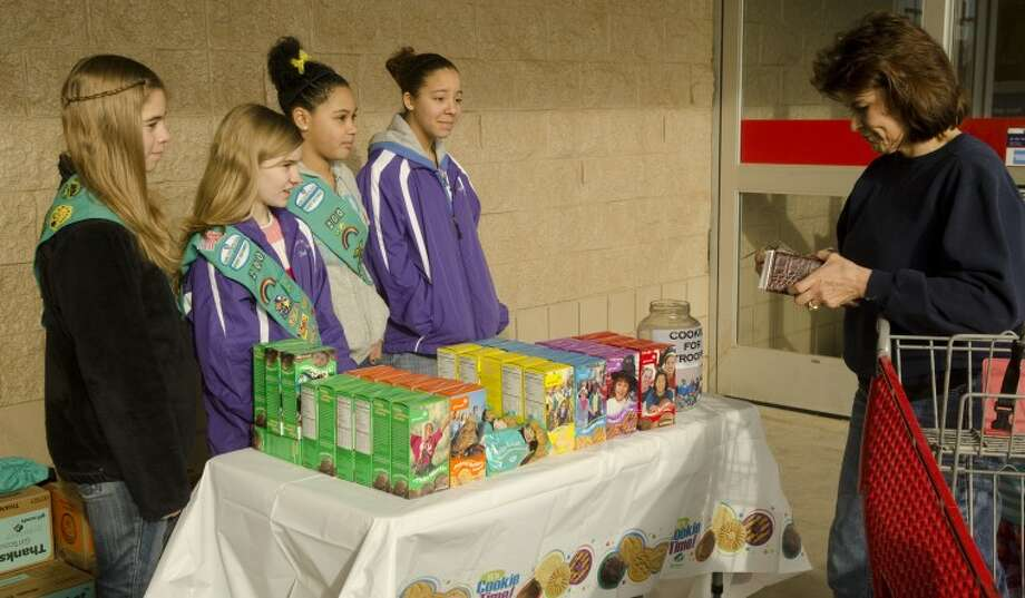 Laurel Utsman, Chastin Ellison, Eden Brown and McKenzey Jackson wait as Jackie Burkholder decides what Girl Scout cookies she wants Saturday outside Lowes. Photo by Tim Fischer/Midland Reporter-Telegram Photo: Tim Fischer
