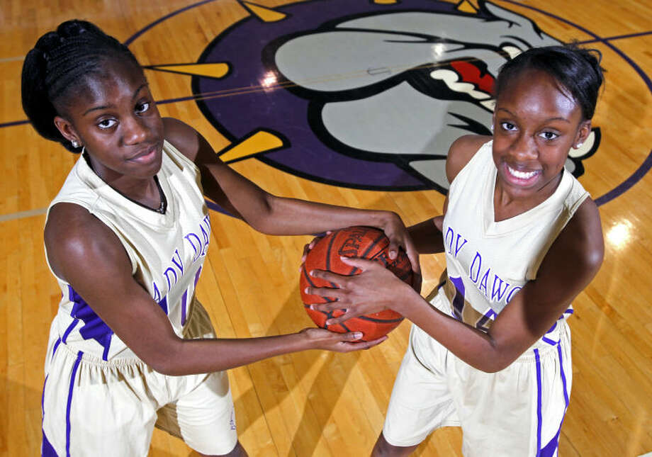 Twins Alexandra Washington, left, and Alexis Washington, right, pose for a portrait Thursday in the Midland High gym. James Durbin/Reporter-Telegram Photo: JAMES DURBIN