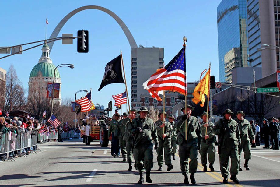 FILE - In this Jan. 28, 2012 file photo, participants in a parade to honor Iraq War veterans make their way along a downtown street in St. Louis. The parade welcoming home Iraq War and other post-Sept. 11 veterans was such a hit that at least 10 other cities around the country are considering similar celebrations. (AP Photo/Jeff Roberson, File) Photo: Jeff Roberson / AP