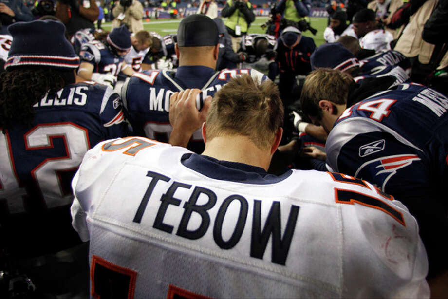 Denver Broncos quarterback Tim Tebow prays with New England Patriots and Broncos team members following an NFL divisional playoff football game Saturday, Jan. 14, 2012, in Foxborough, Mass. The Patriots defeated the Broncos 45-10. (AP Photo/Charles Krupa) Photo: Charles Krupa / AP