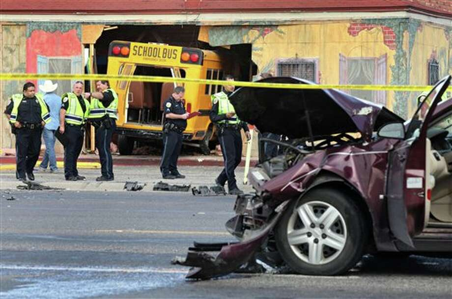 Emergency personnel work the scene of a fatal three-vehicle accident involving a Jeep, an Impala and a Daystar Kids Learning Center school bus Thursday, Feb. 2, 2012, at Andrews Highway and West 21st Street in Odessa, Texas. No children were in the bus at the time of the accident. According to Cpl. Sherrie Carruth, the female bus driver ran a stop sign on West 21st Street and collided with both southbound vehicles before crashing into the former Ajuua's restaurant. The bus driver, who the Odessa Police Department identified as Victoria Garcia, was found lying on the road and died soon afterward at the hospital. The driver of the Jeep was transported with non life-threatening injuries, and the Impala driver and his two-year-old son who also was in the vehicle are uninjured. (AP Photo/Odessa American, Heather Leiphart) Photo: Heather Leiphart / Odessa American