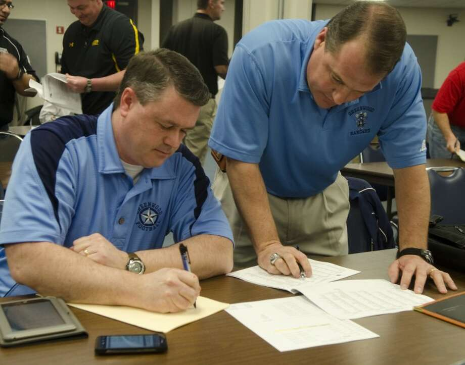 (File Photo) Greenwood coaches Doug Young and Shad Hanna look over and make notes on the just released UIL realignment paperwork Thursday morning at the Region 18 Service Center. Photo by Tim Fischer/Midland Reporter-Telegram Photo: Tim Fischer