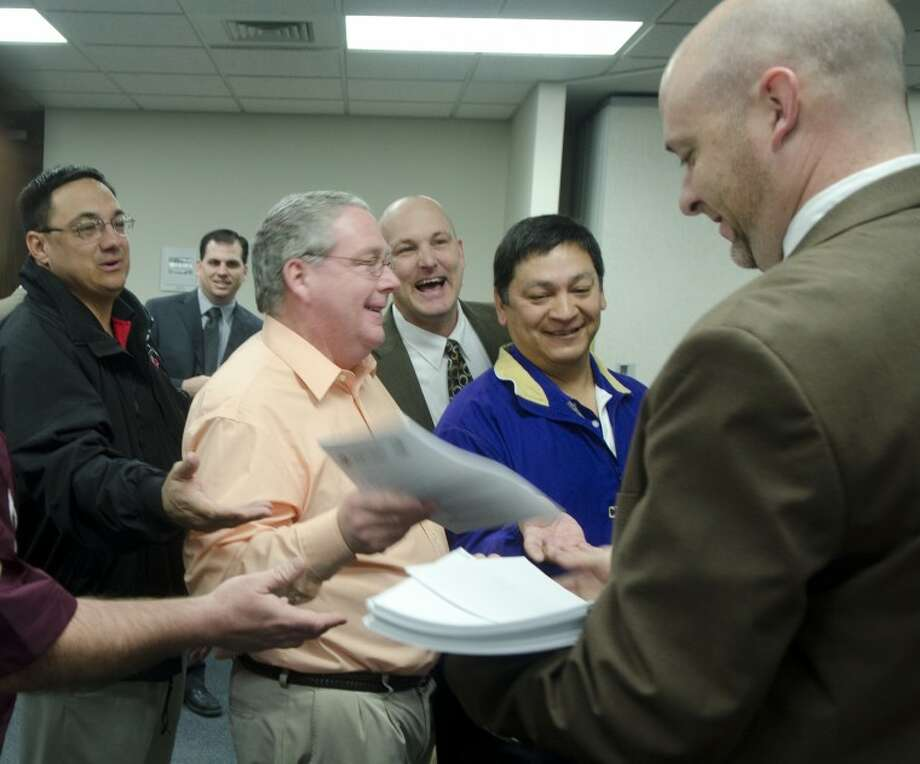 John Petree, right, assistant exeutive director of Region 18, hands out the packets listing UIL realignment Thursday to eager coaches and staff at the Region 18 Service Center. Photo by Tim Fischer/Midland Reporter-Telegram Photo: Tim Fischer