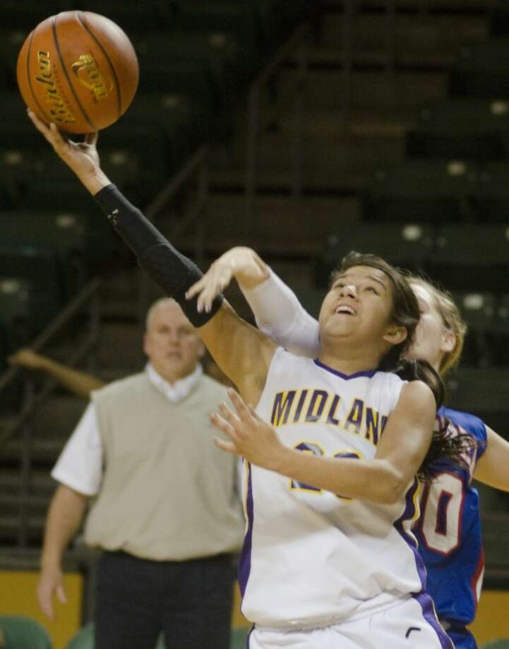 Midland High's Elaine Herrera gets fouled by Abilene Cooper's Madison Daniels as she goes up for a shot Tuesday evening at the Chap Center. Photo: Tim Fischer