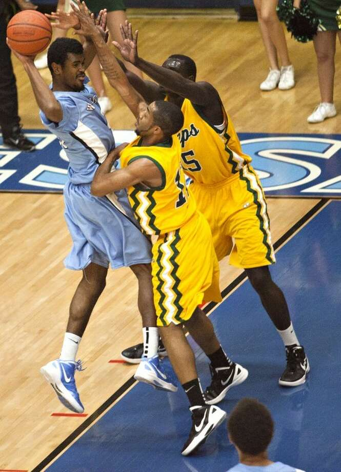 Odessa College's Matthew Hunter (25) passes as Midland High's Majok Majok (15) and Kalvin Agee (12) pressure him during the game Monday at the OC Sports Center. Albert Cesare/Odessa American Photo: Albert Cesare|Odessa American