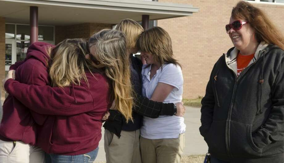 """Sandy Childers, center, hugs McKayla Massey as Janet """"Georgia"""" Scott, right, and others gather Tuesday outside Lee Freshman to show support for any teens needing to talk. Photo by Tim Fischer/Midland Reporter-Telegram Photo: Tim Fischer"""