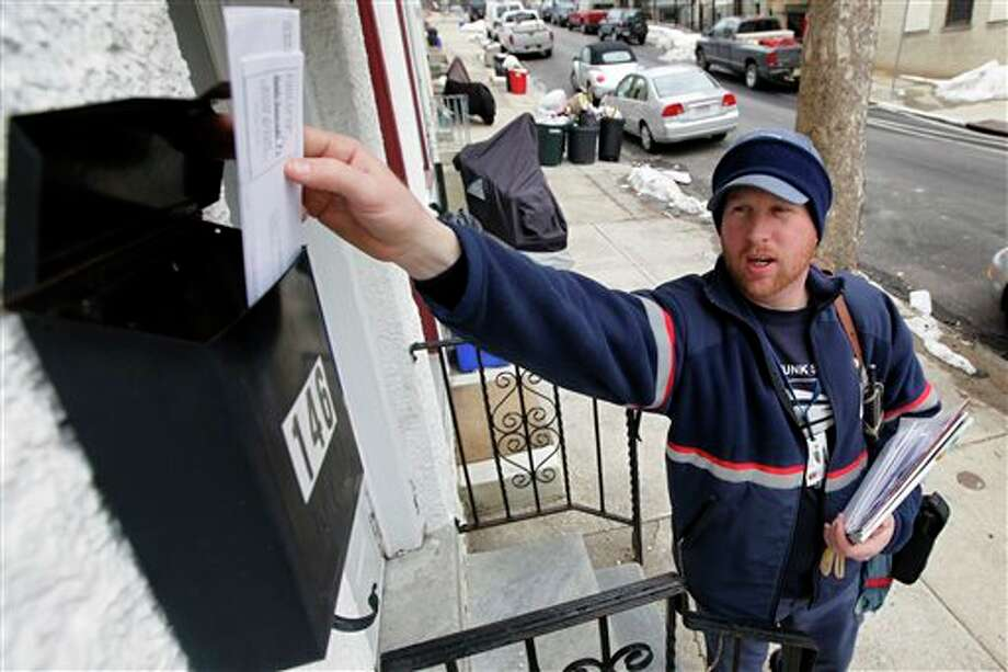 FILE - In this Tuesday, March 2, 2010 file photo, letter carrier Kevin Pownall delivers mail in Philadelphia. The financially struggling U.S. Postal Service announced on Wednesday, Feb. 6, 2013 it will stop delivering mail on Saturdays but continue to deliver packages six days a week under a plan aimed at saving about $2 billion a year. (AP Photo/Matt Rourke, File) Photo: Matt Rourke / AP