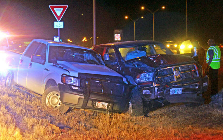 Midland police and Department of Public Safety troopers investigate the cause of a two-pickup collision Wednesday night on Interstate 20. Tyler White/Reporter-Telegram Photo: TYLER WHITE