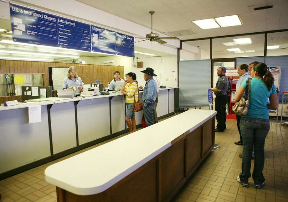 (File Photo) Postal workers assist customers with their postal needs Monday at the downtown post office. Monday is also the last day to have your tax returns post marked and sent. Cindeka Nealy/Reporter-Telegram Photo: Cindeka Nealy