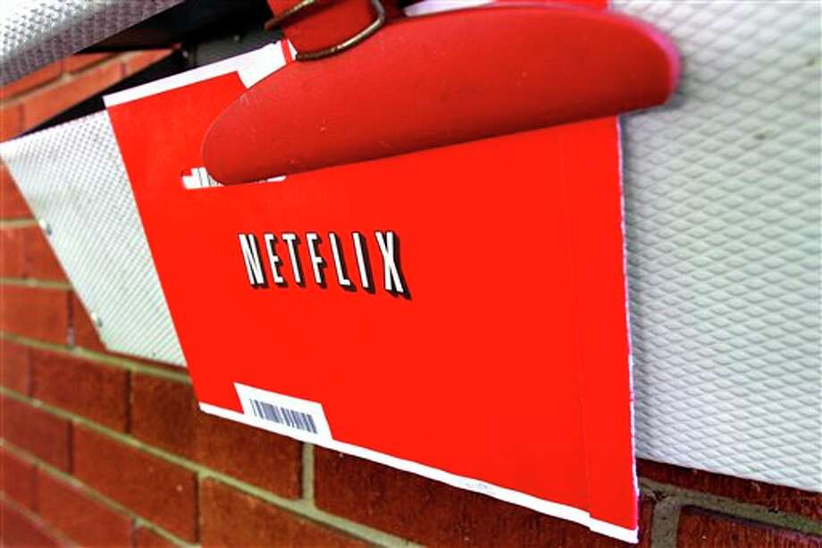 FILE - In this Thursday, Aug. 23, 2012, file photo, a Netflix envelop containing a DVD to be returned by mail is clipped onto a mailbox, in Springfield, Ill. Netflix won't miss Saturday mail delivery, even though the weekend service helped keep its DVD-by-mail subscribers happy. The U.S. Postal Service's planned shift to five days of home delivery a week instead of six may even make Netflix Inc. slightly more profitable. (AP Photo/Seth Perlman) Photo: Seth Perlman / AP