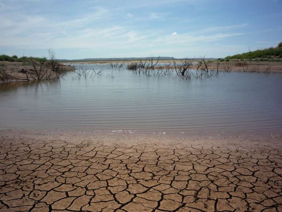 The dwindling water at Spence Reservoir fades from its now deeply cracked former floor. Photo: John Boyd/MRT