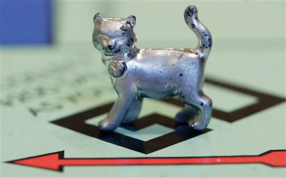 The newest Monopoly token, a cat, rests on the game board at Hasbro Inc. headquarters, in Pawtucket, R.I., Tuesday, Feb. 5, 2013. Voting on Facebook determined that the cat would replace the iron token. (AP Photo/Steven Senne) Photo: Steven Senne / AP